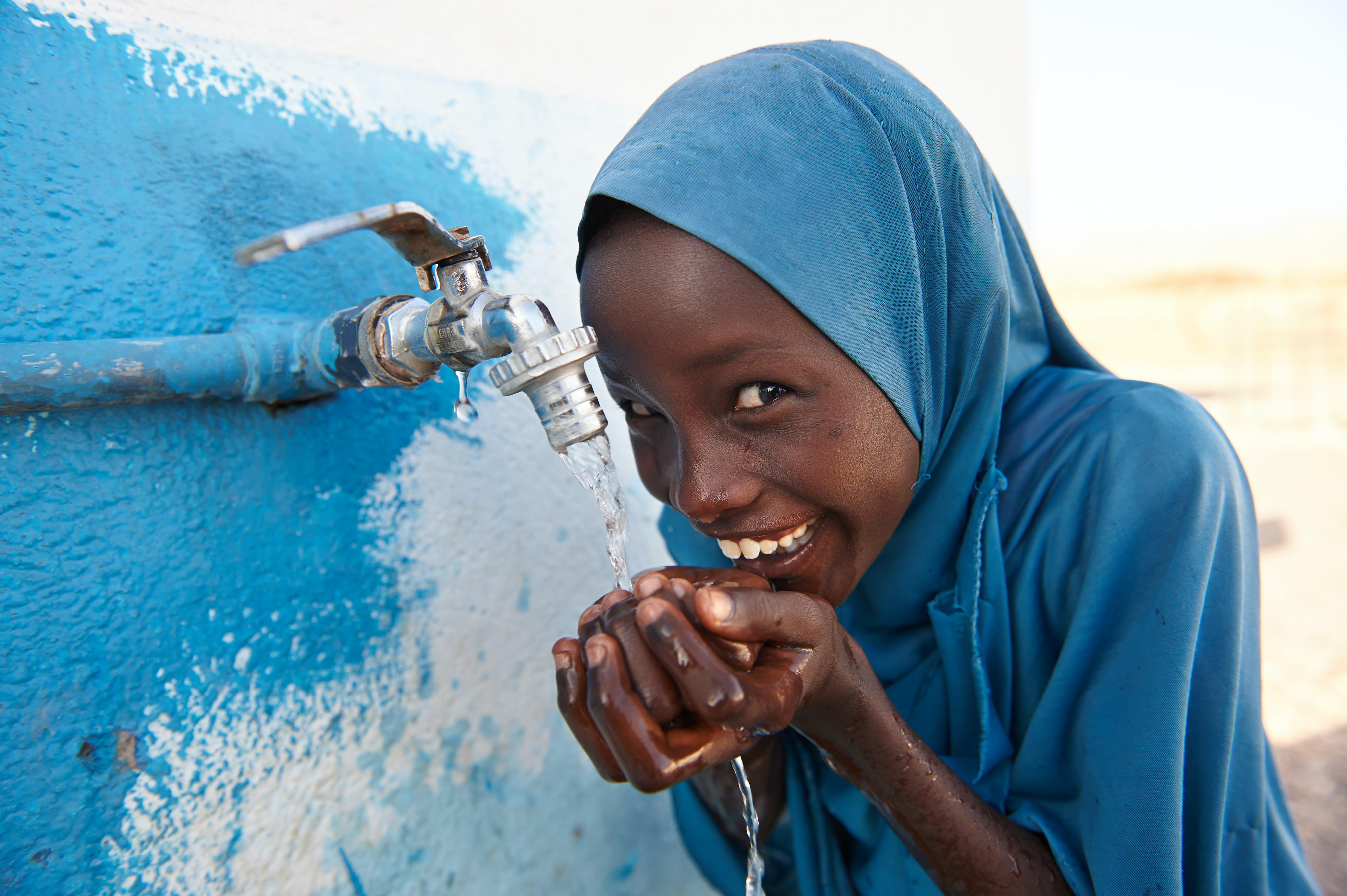 Bambina sorridente beve ad una fontanella