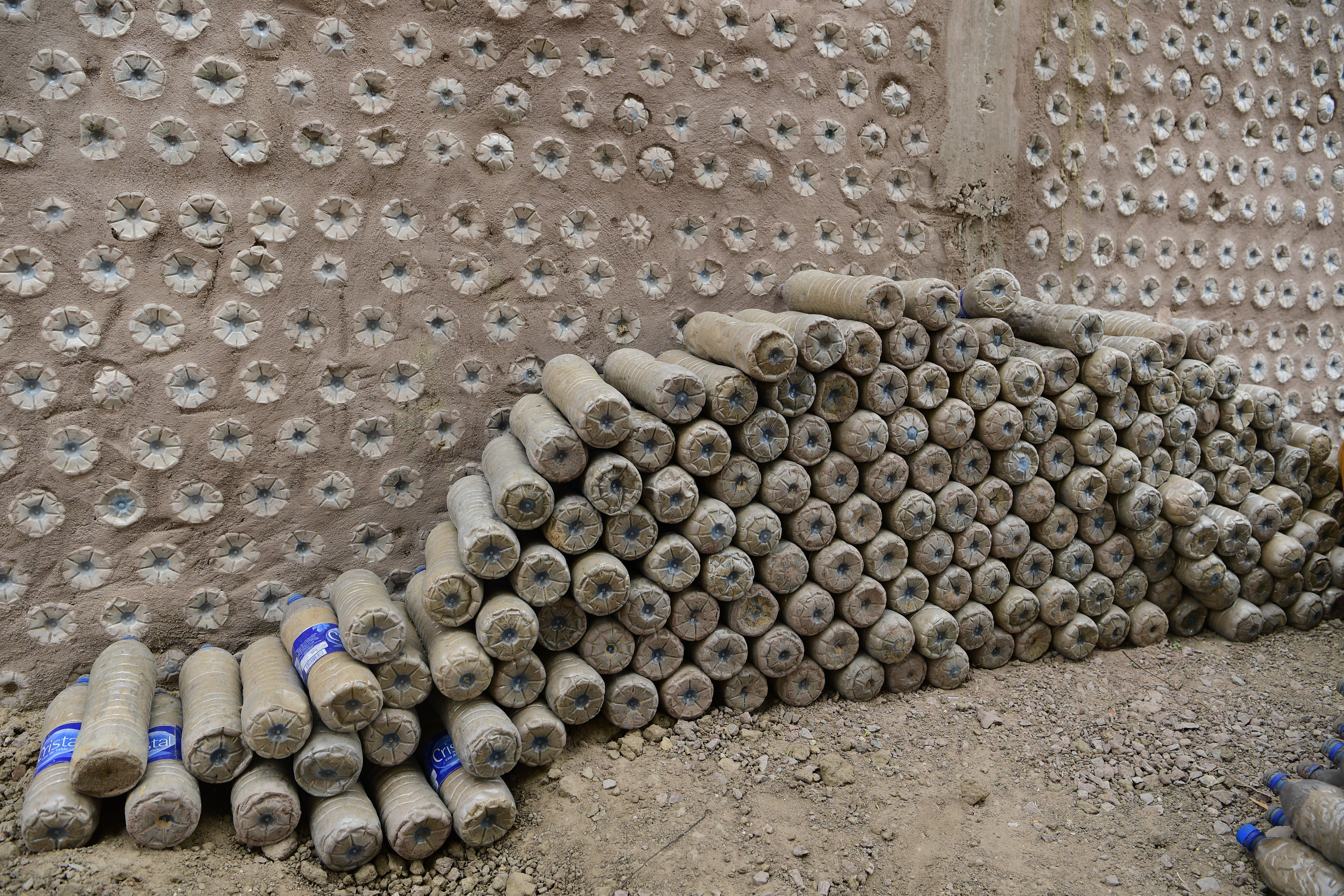 Le bottiglie riempite di sabbia vengono impilate per costituire la parete della scuola