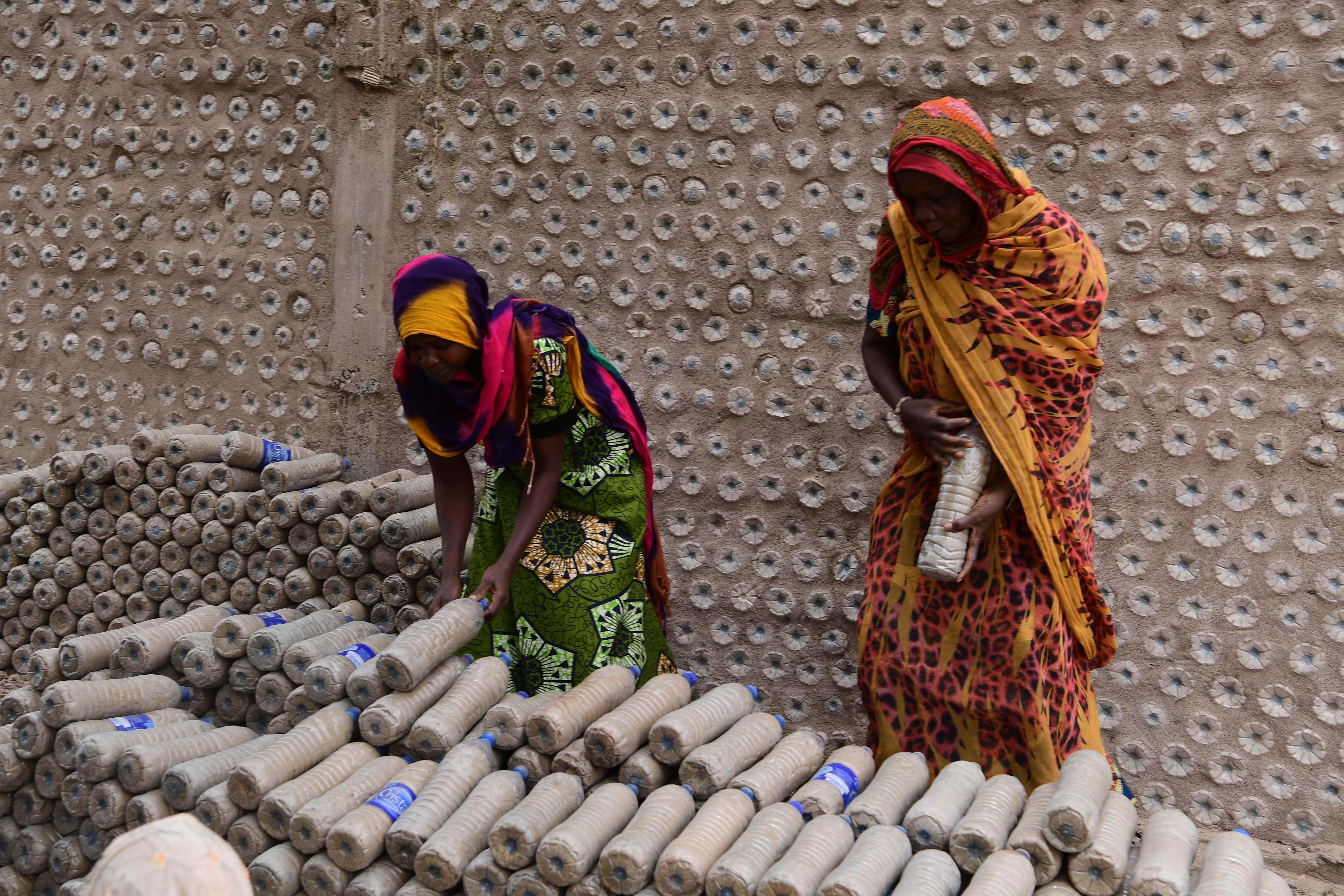 Due donne dispongono le bottiglie in modo ordinato: costituiranno la parete della nuova classe