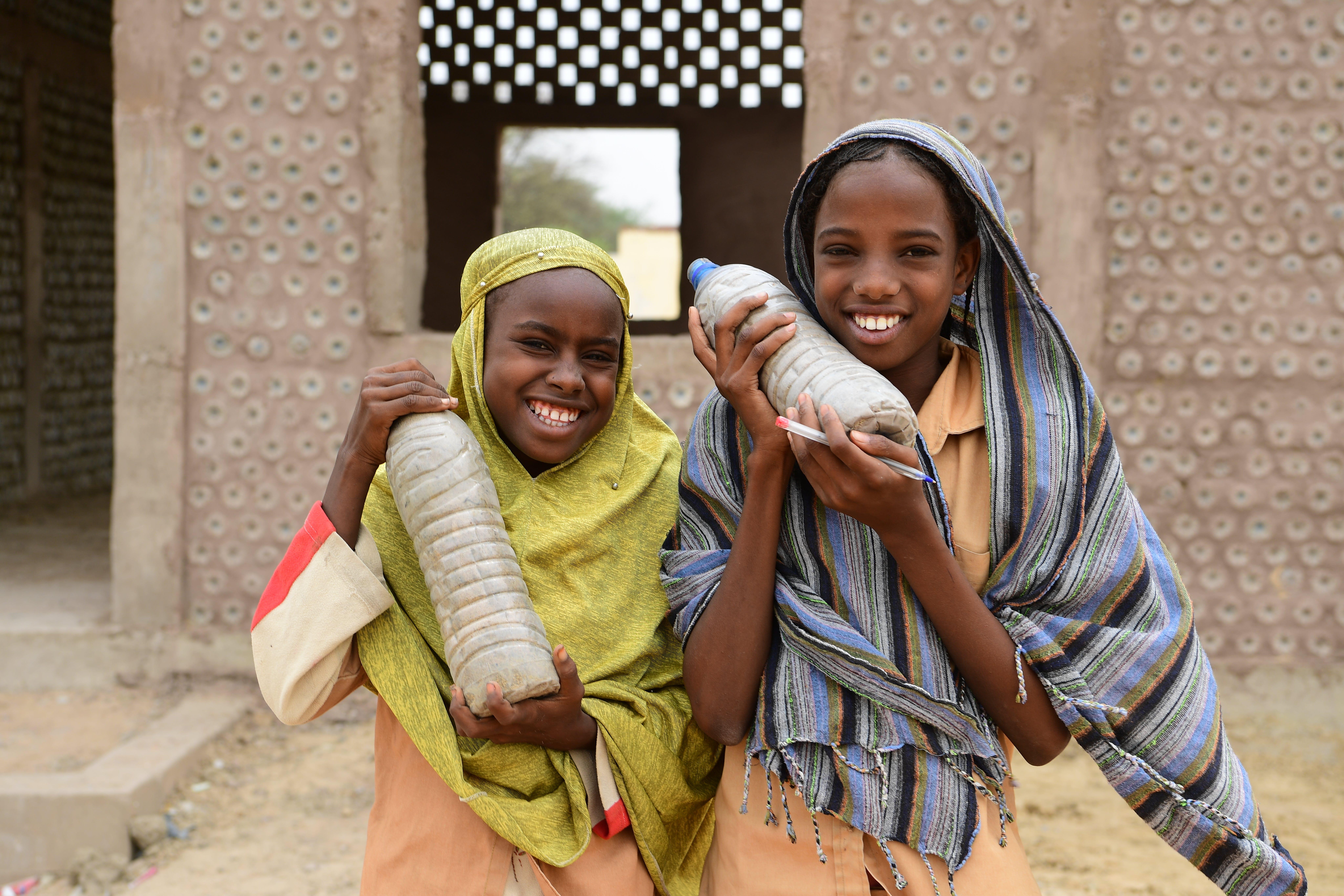 Ciad, due bambine mostrano le bottiglie di plastica con cui è stata costruita la loro nuova classe