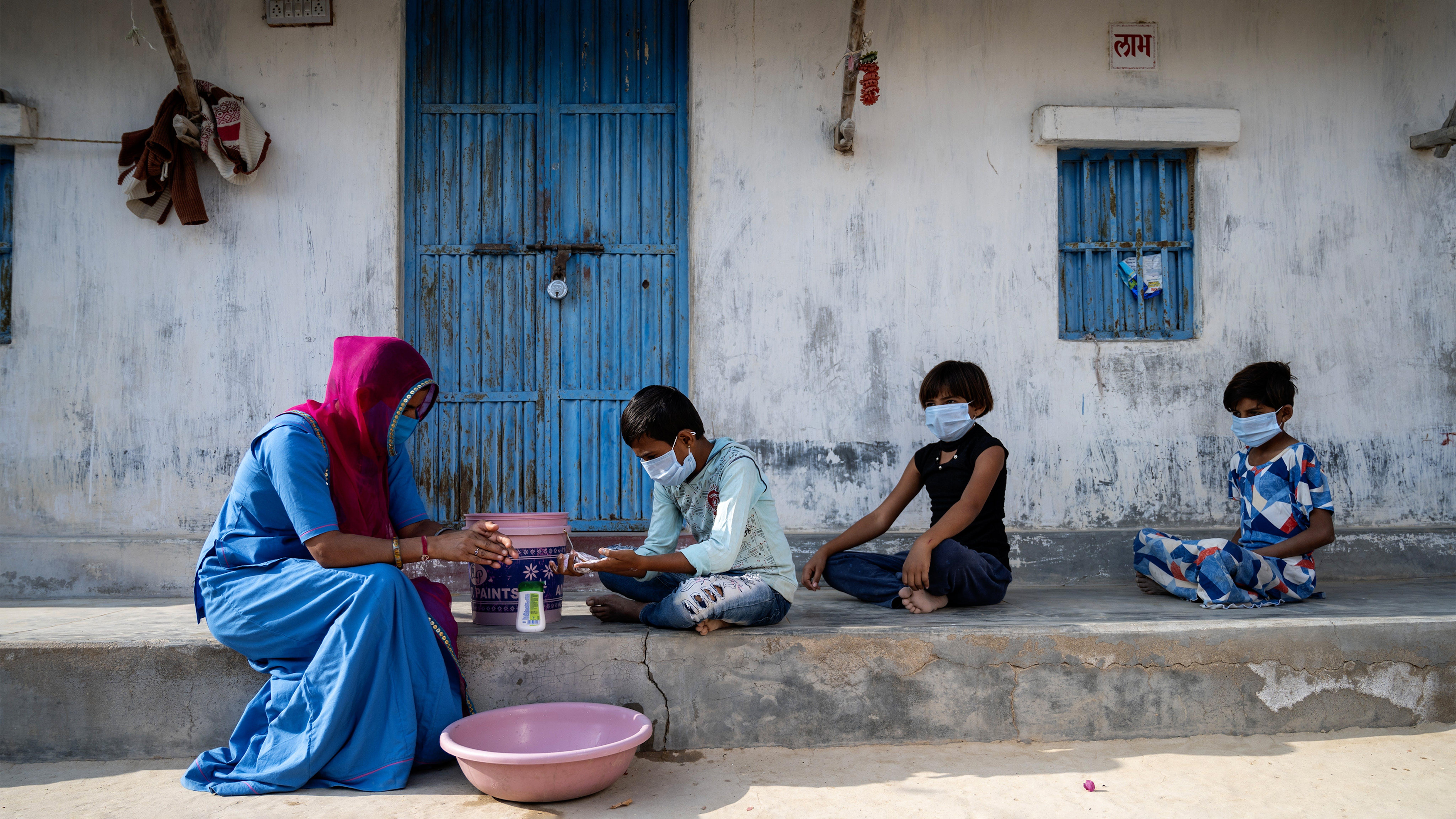 India,  Asha Laxmi, un operatore sociale.  conduce una sessione di lavaggio delle mani nelle case del villaggio durante la pandemia di covid 19