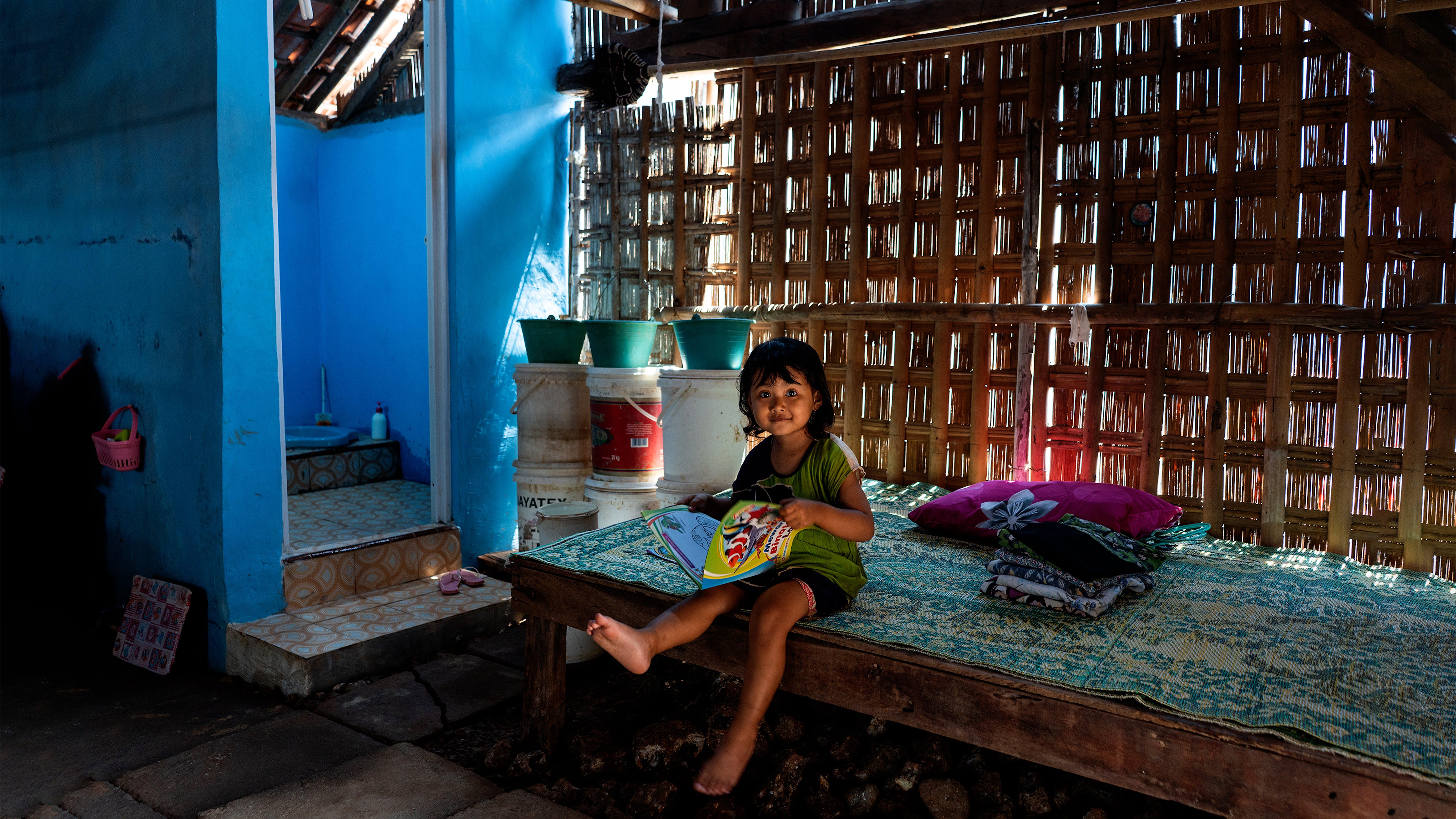 Indonesia, Fika, 3 anni, legge un libro vicino a un bagno di nuova costruzione nella sua casa nel villaggio di Tegaldowo