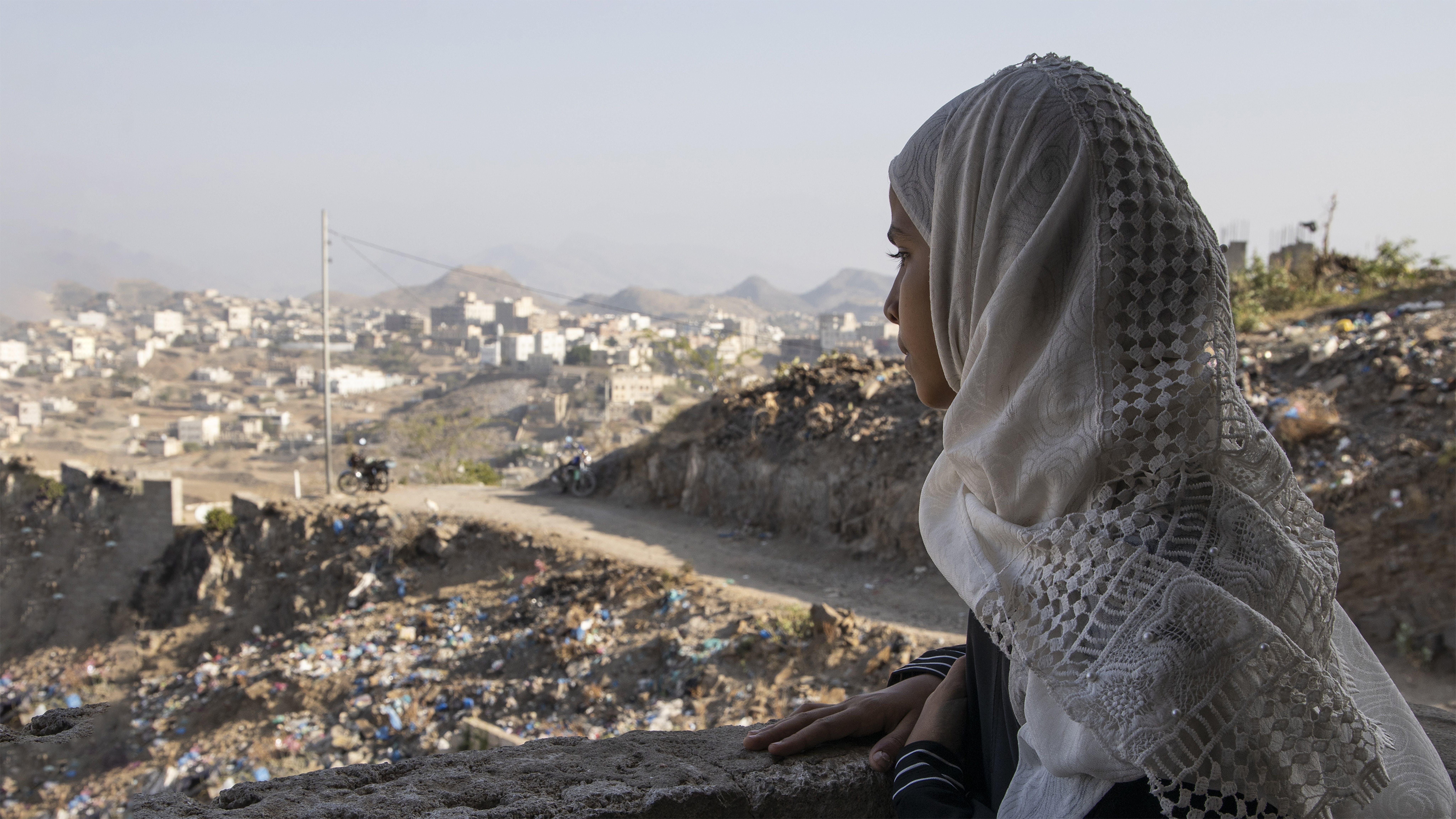 Yemen, una ragazza guarda le rovine della città di Taizz dalla sua scuola dove fa lezioni