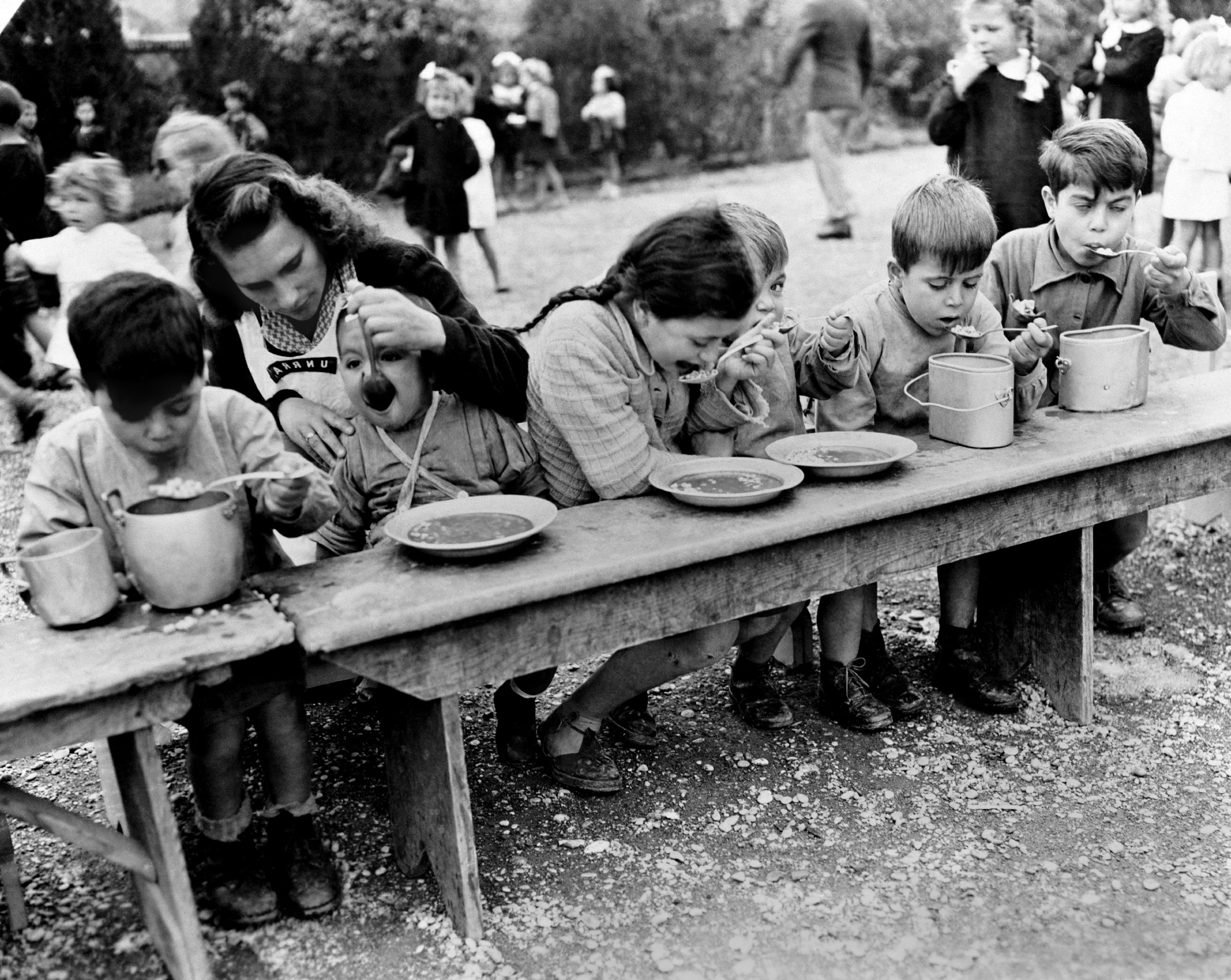 Italia, 1945: tavolata di bambini che ricevono un pasto dall'UNRRA, a sostegno delle popolazioni vittime della guerra