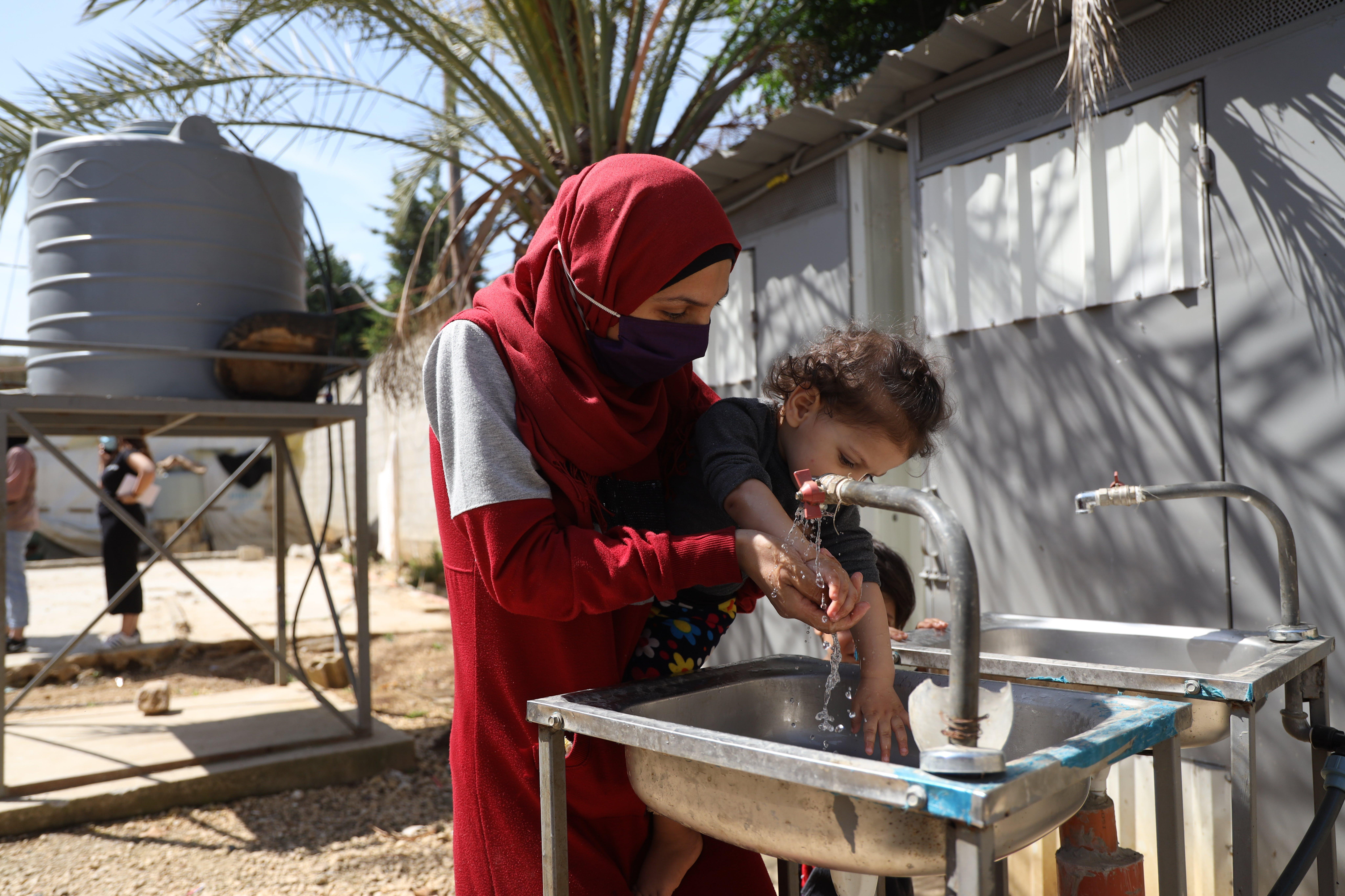 Una mamma lava le mani alla figlia di un anno nel campo rifugiati informale di Mhamara