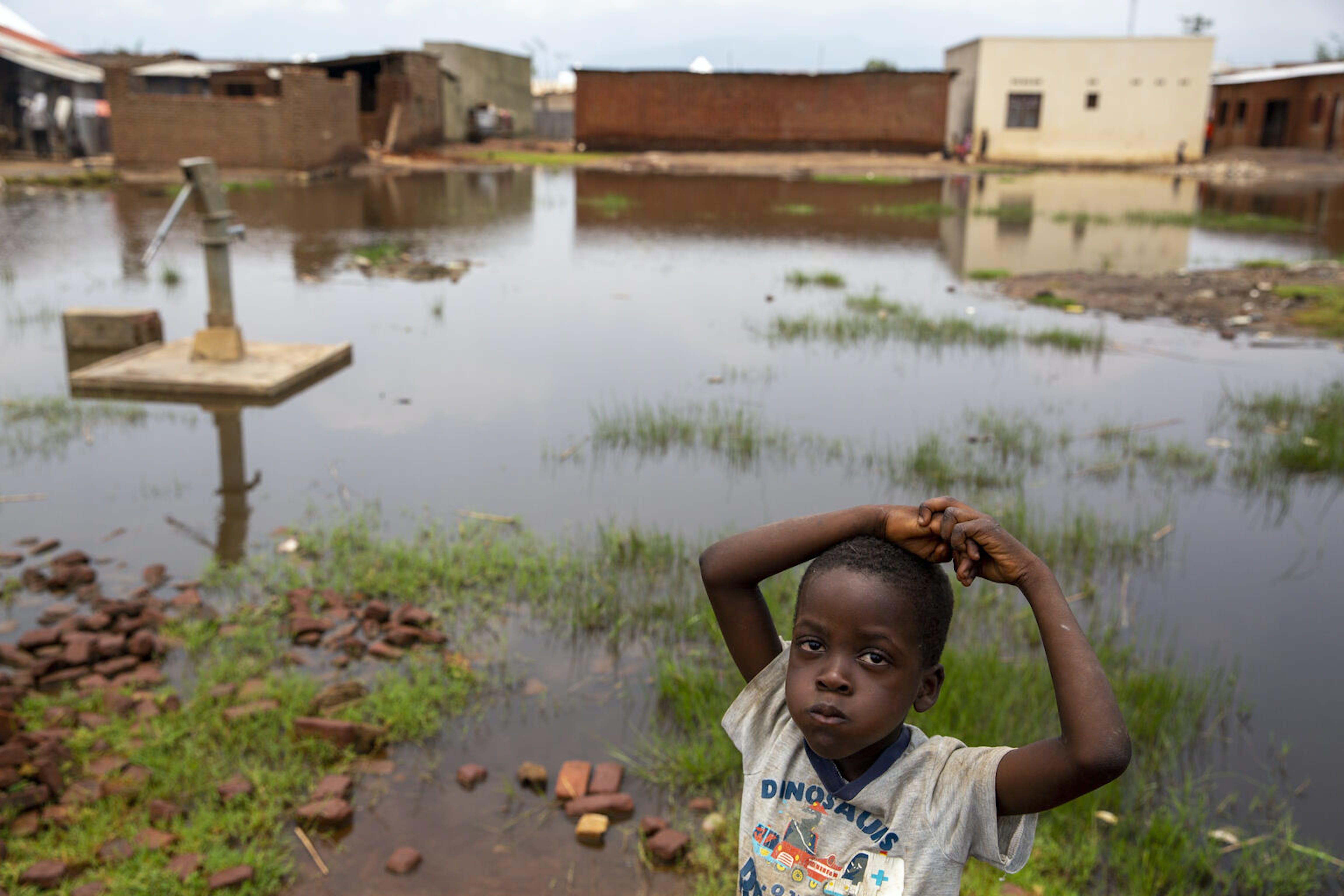 Un bambino vicino a una pompa per l'acqua sommersa a causa delle alluvioni, a Gatumba, vicino a Bujumbura in Burundi. 5 marzo 2021