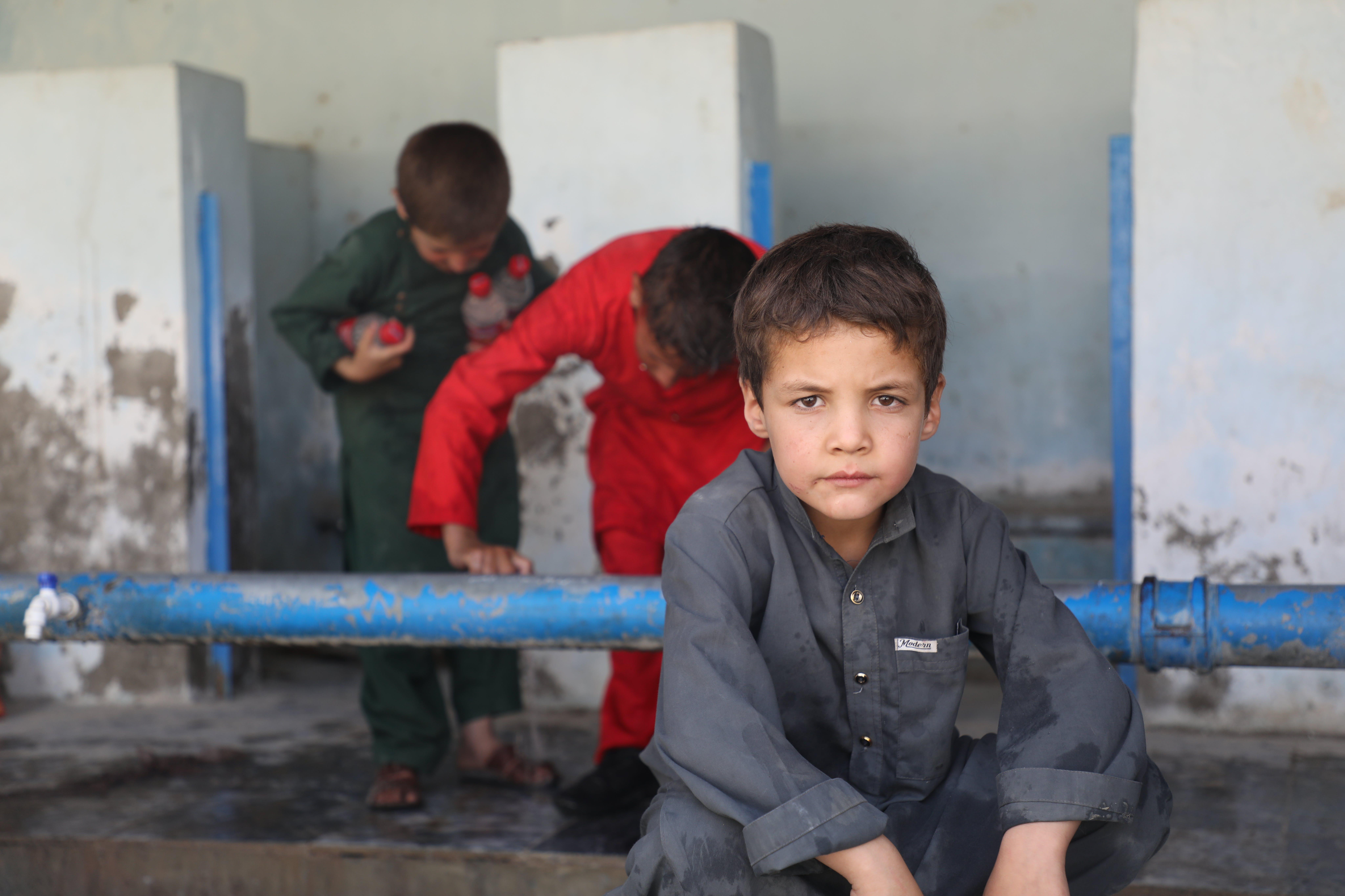 Kabul, un bambino guarda fisso in camera. Sullo sfondo la scuola di Peer Mohammad Kakar dove vivono oltre 400 famiglie di sfollati che hanno bisogno di assistenza immediata
