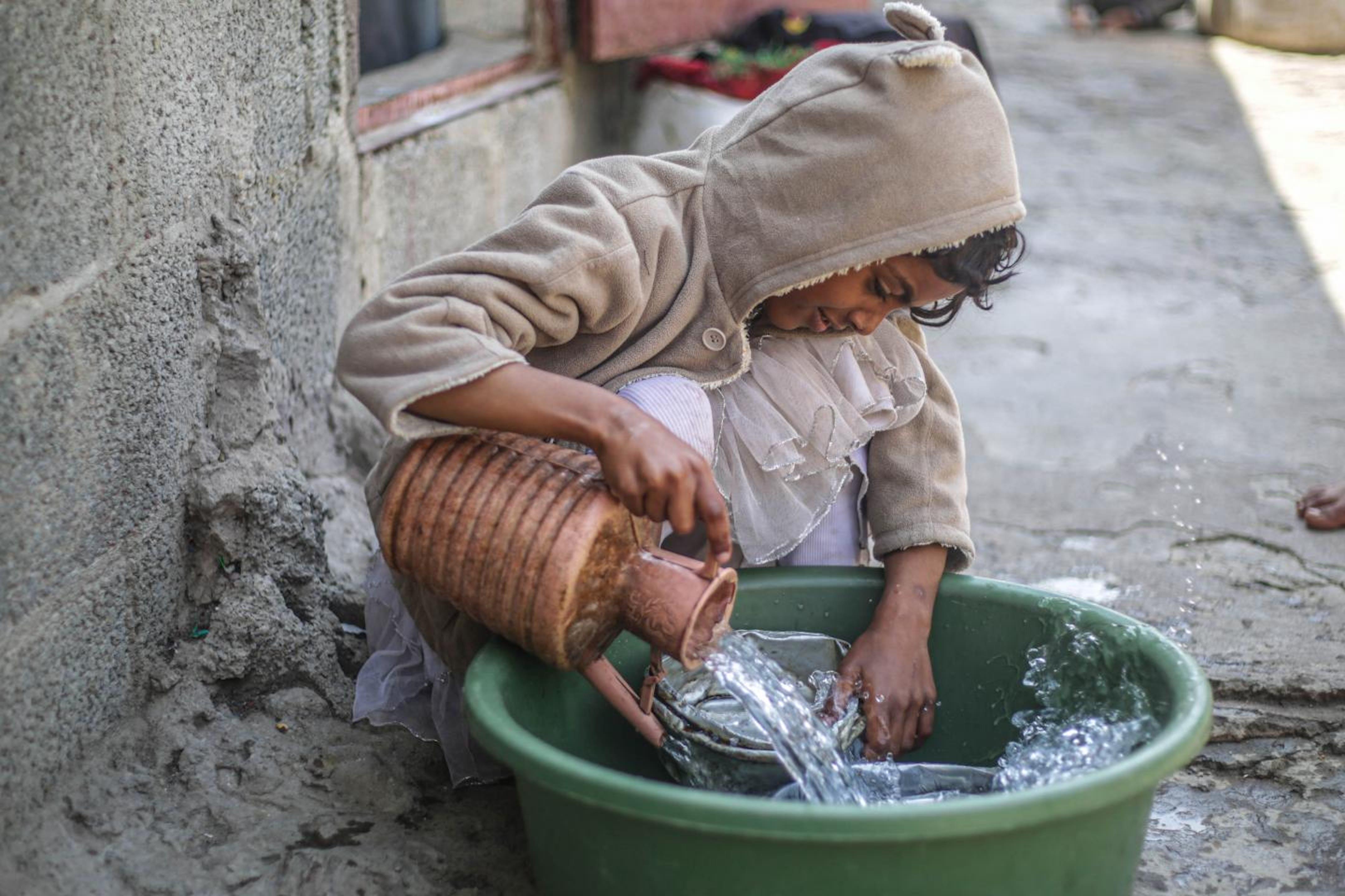Yemen: Sara Fawzi, 14 anni, in un campo per sfollati con la sua famiglia lava i piatti. L'acqua è tornata disponibile grazie al ripristino del pozzo con il sostegno dell'UNICEF