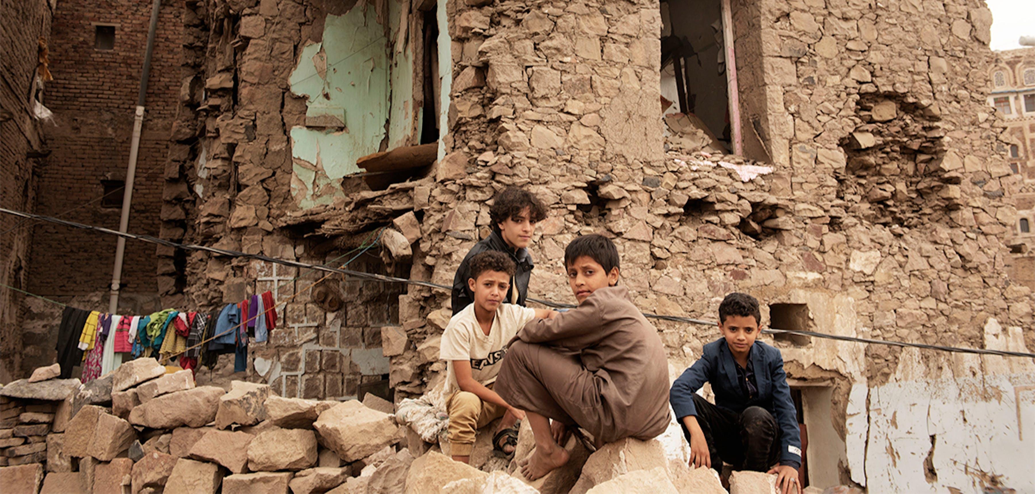 Yemen, bambini si trovano di fronte a un edificio distrutto dai bombardamenti