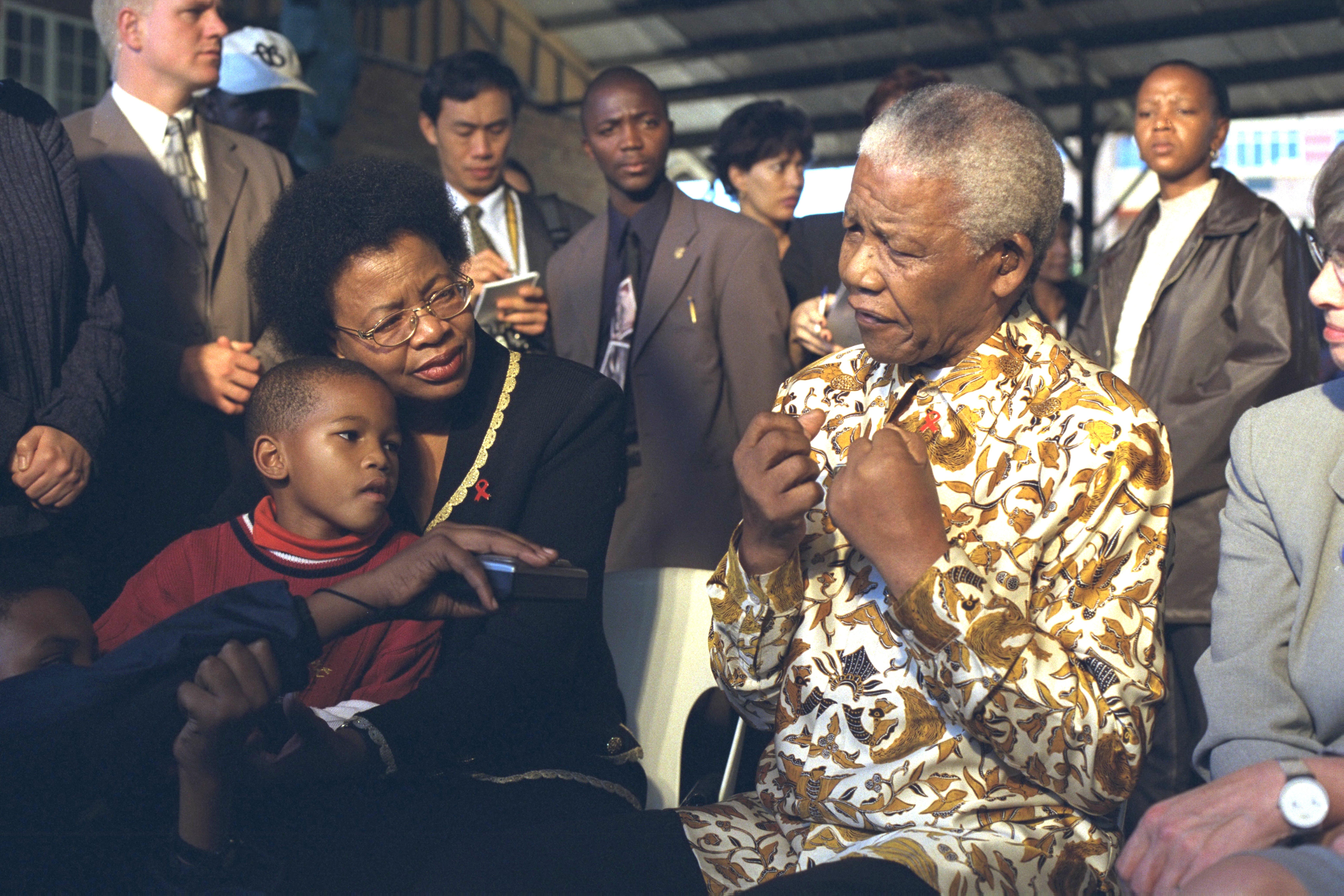 Sudafrica, 2000: Graca Machel tiene in braccio un bambino mentre Nelson Mandela risponde ad alcune domande alla fine di un evento presso l'Afrikan Cultural Centre.