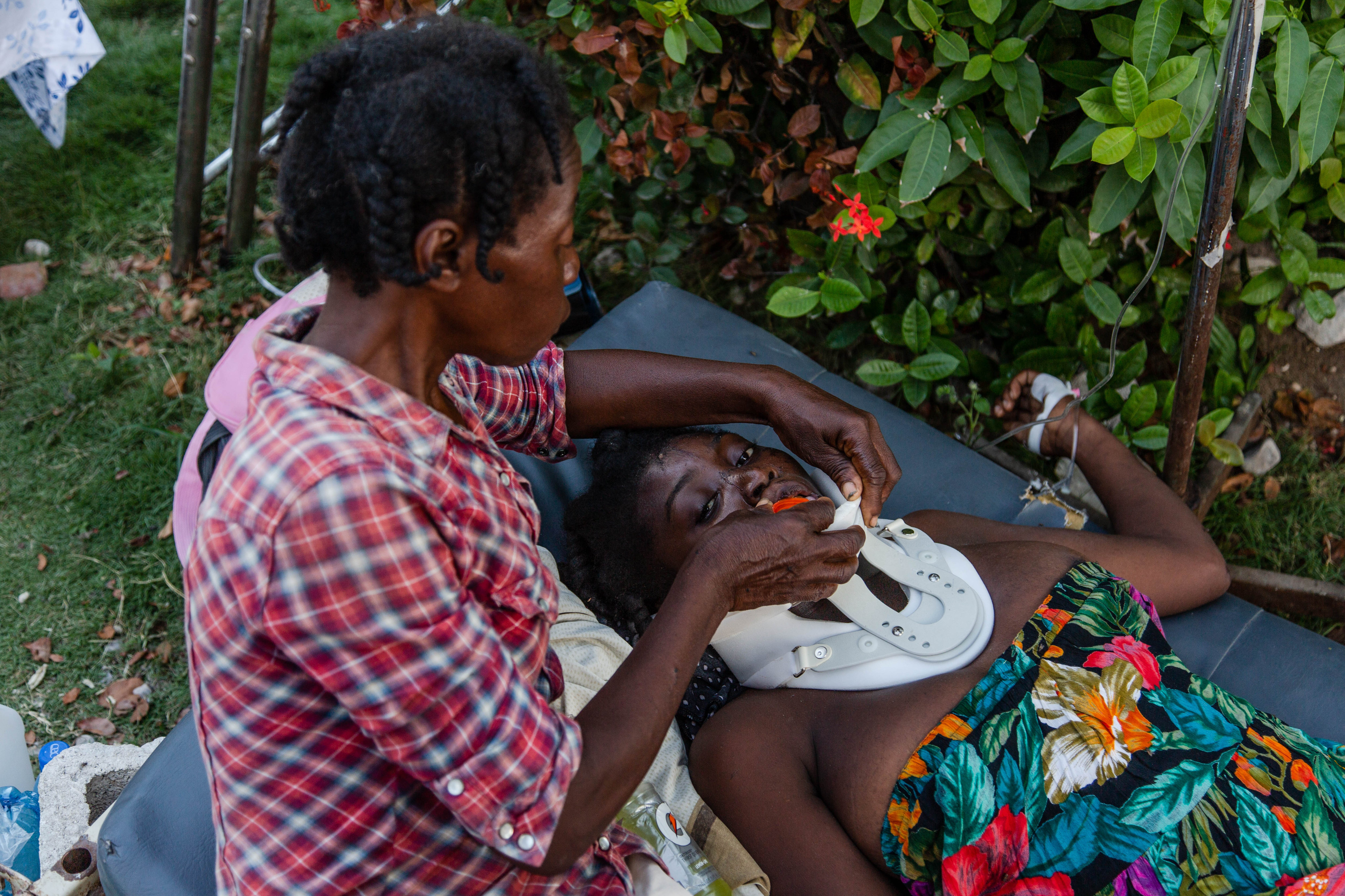 Gerline, una donna rimasta paralizzata al seguito del crollo della sua casa durante il terremoto di Haiti, viene aiutata da un'amica a reidratarsi