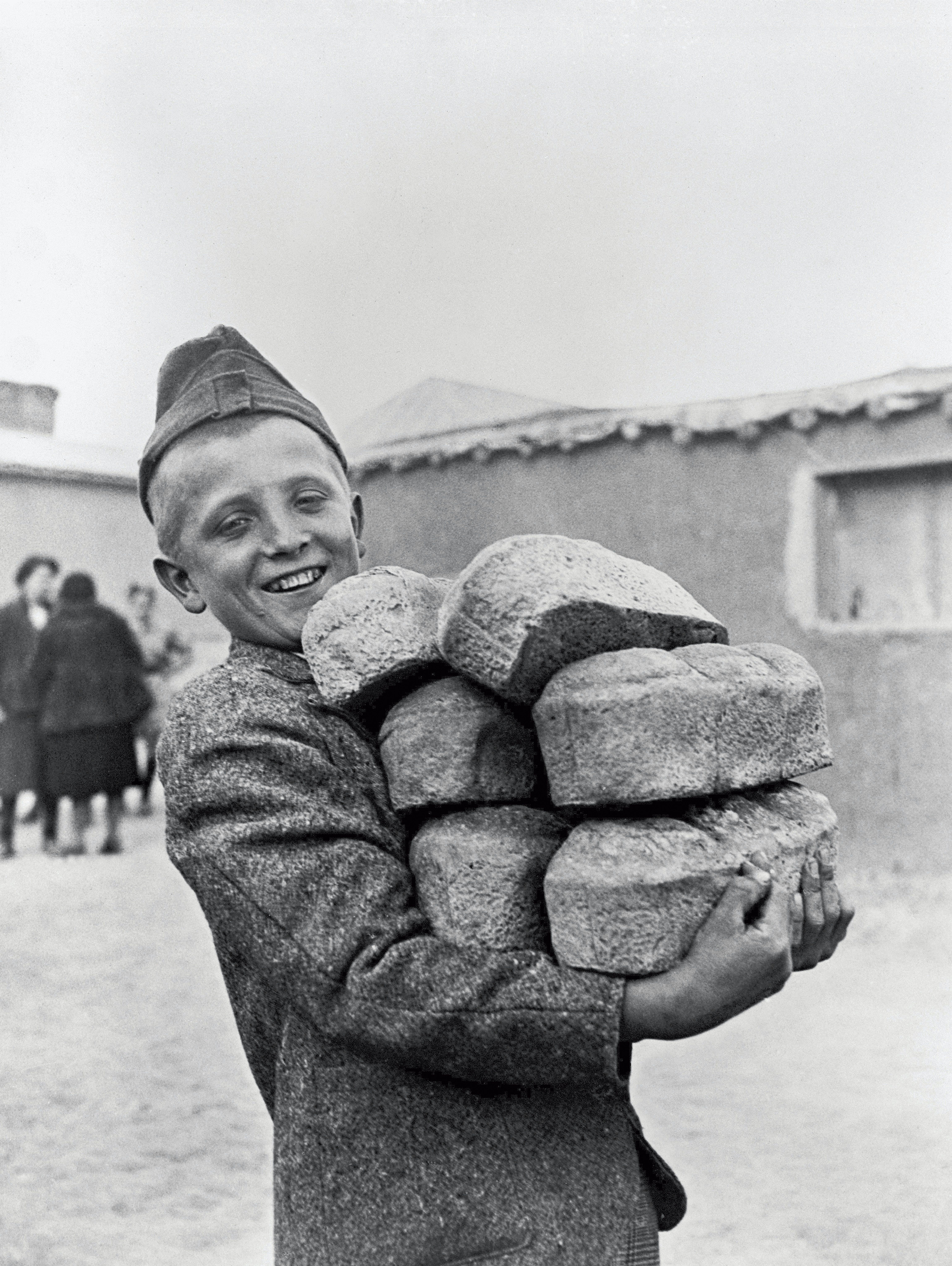 Polonia, 1946: un ragazzo sorride mentre trasporta 6 filoni di pane
