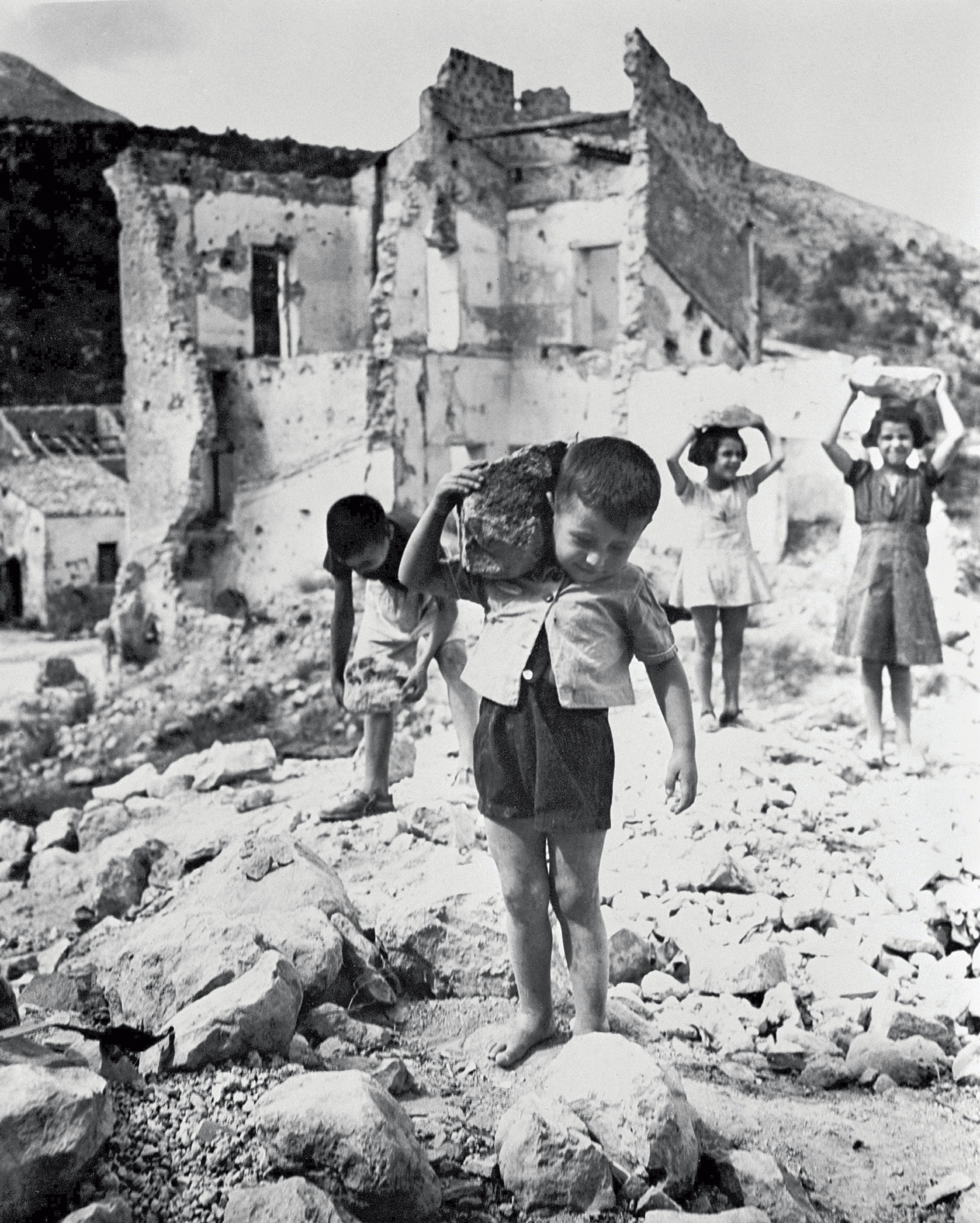 Italia, 1946: alcuni bambini, la maggior parte scalzi, trasportano sassi da un edificio distrutto dalla guerra,  per aiutare a ricostruire la loro città.
