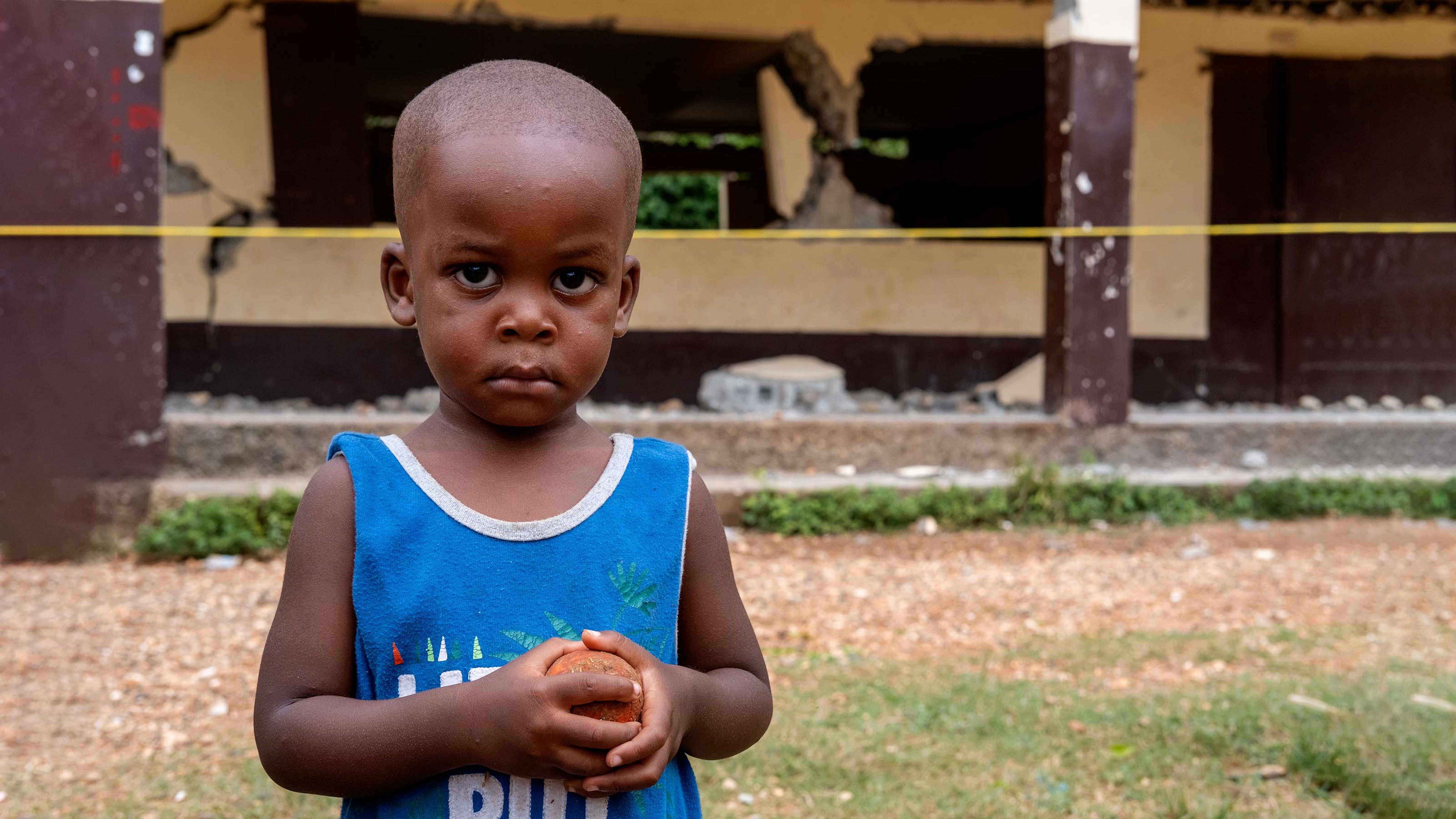 Un bambino si trova di fronte alla sua scuola distrutta durante il terremoto del 2021 ad Haiti.