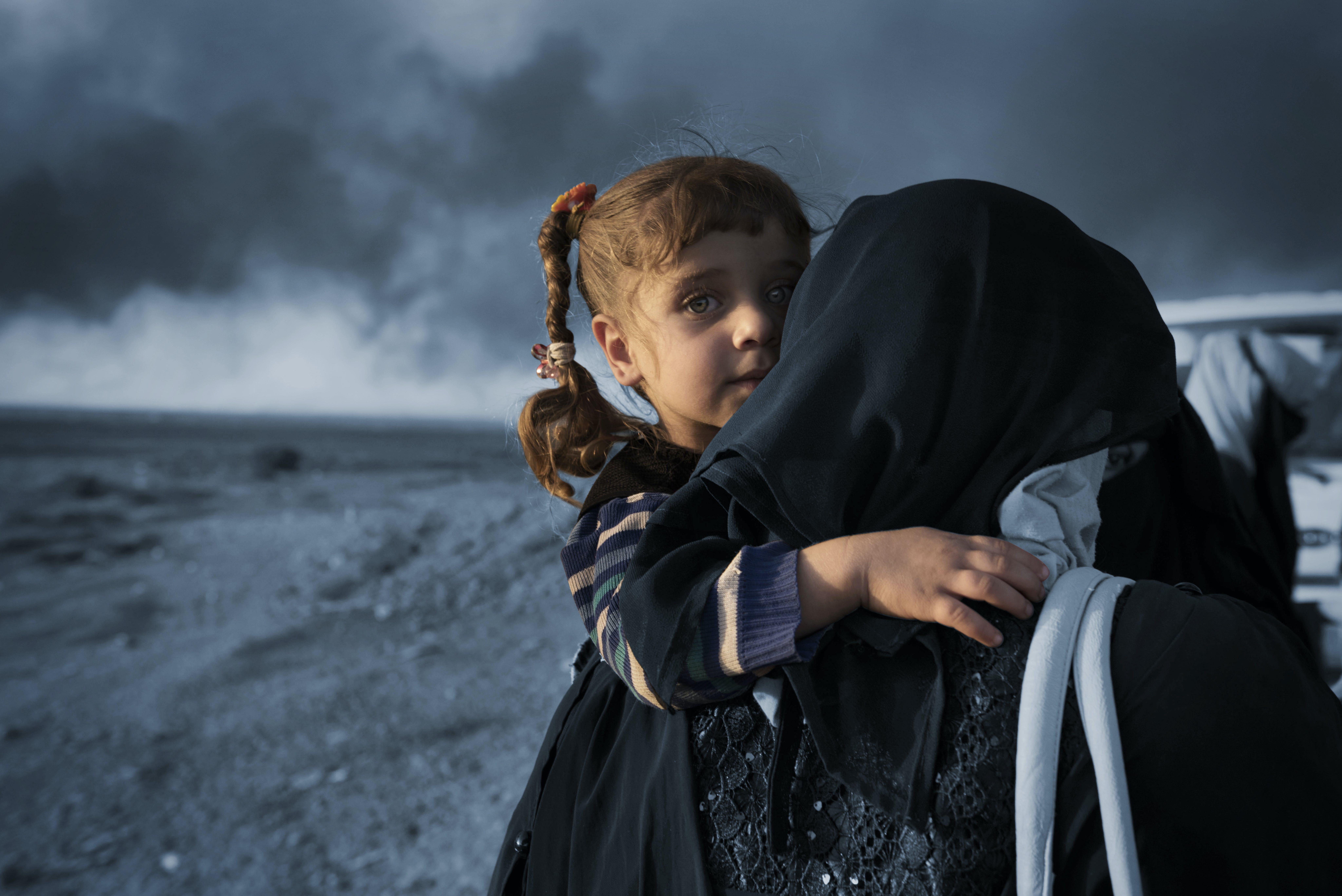 2016: una donna sfollata con la figlia a un posto di blocco a Qayyara, nel sud di Mosul.