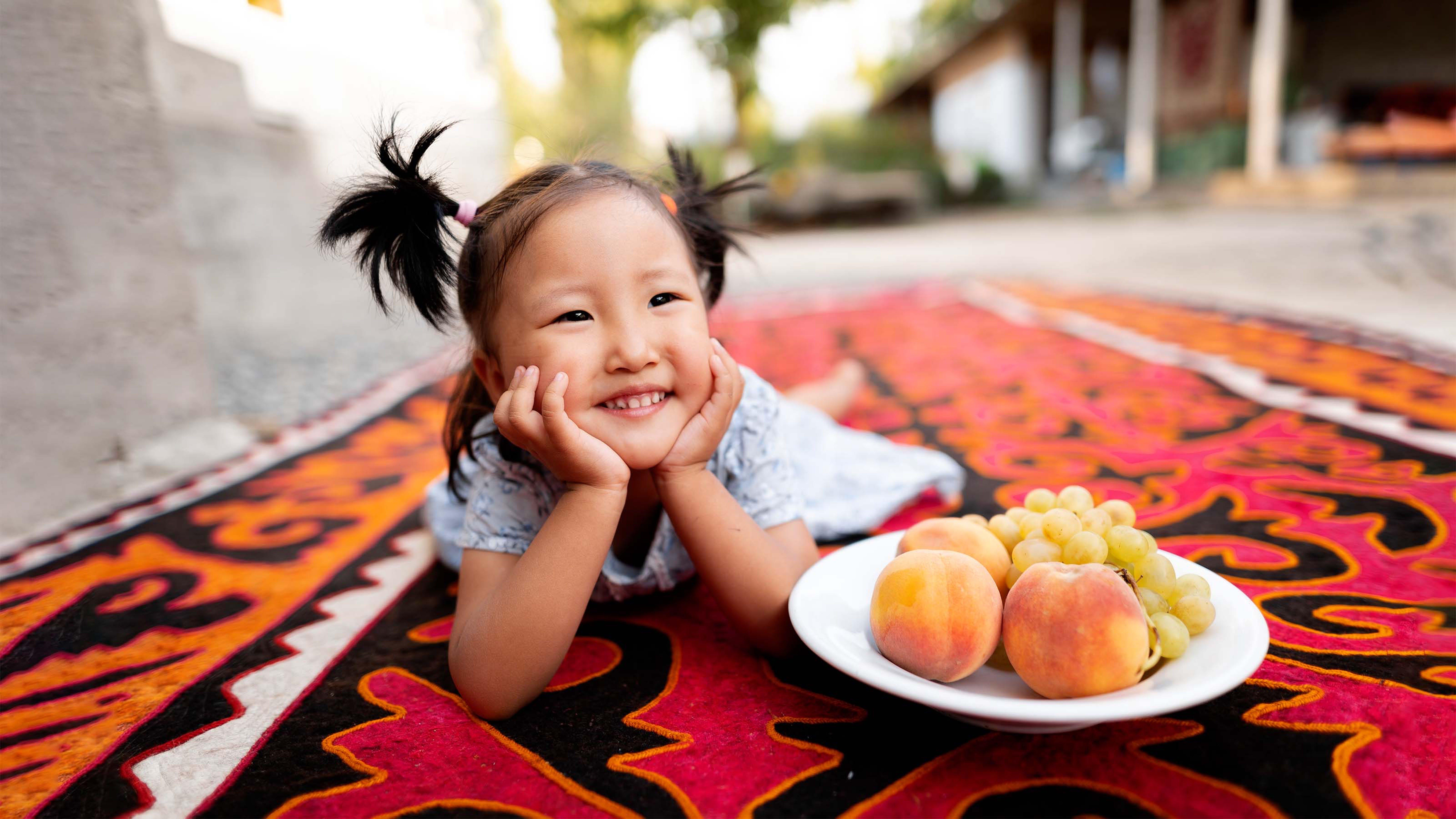 Kyrgyzstan, una bambina con un piatto di frutta, pieno di vitamine