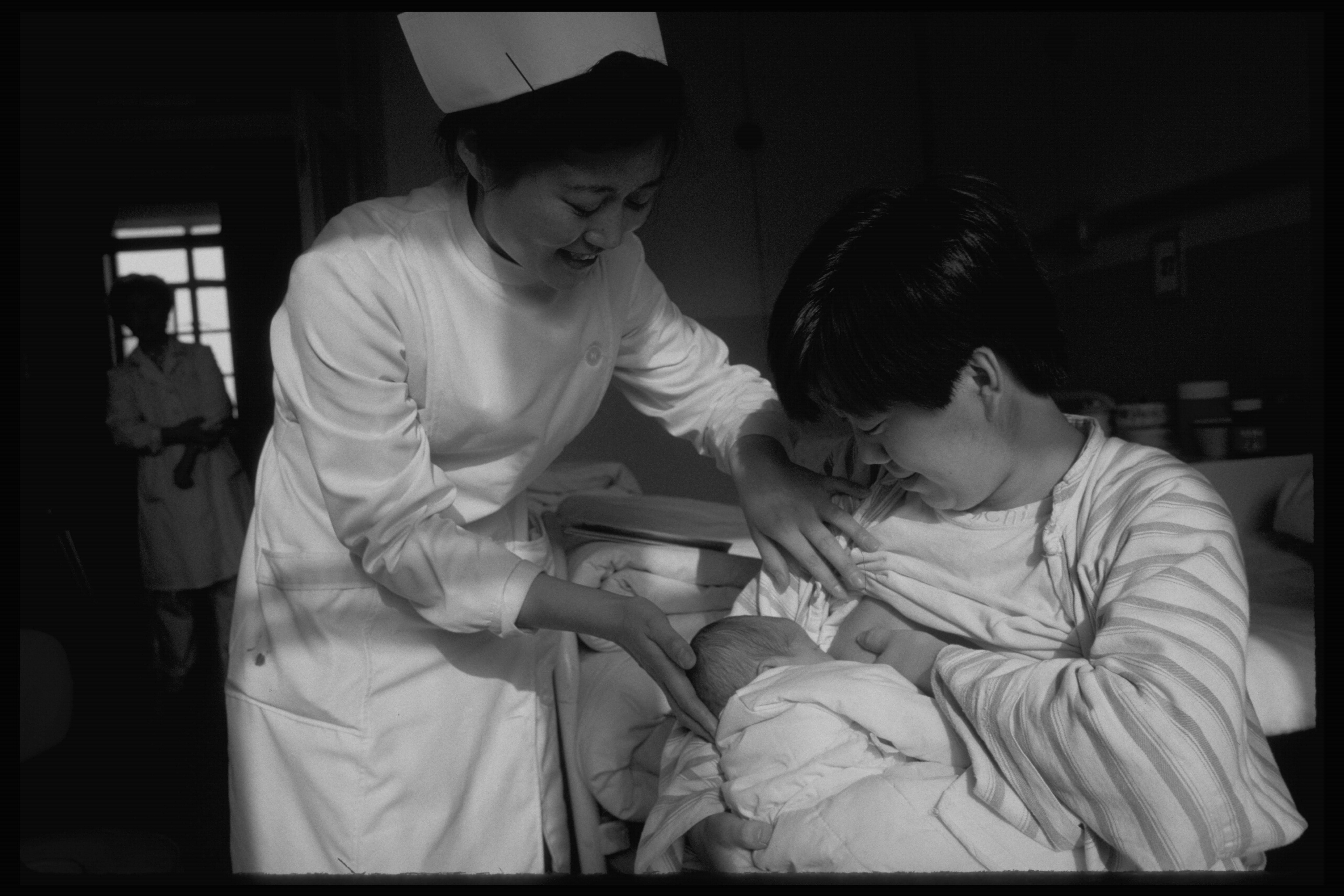1995, Cina: una mamma viene supportata da un'operatrice per l'allattamento al seno, uno dei pilastri per la salute materno-infantile sostenuti dall'UNICEF