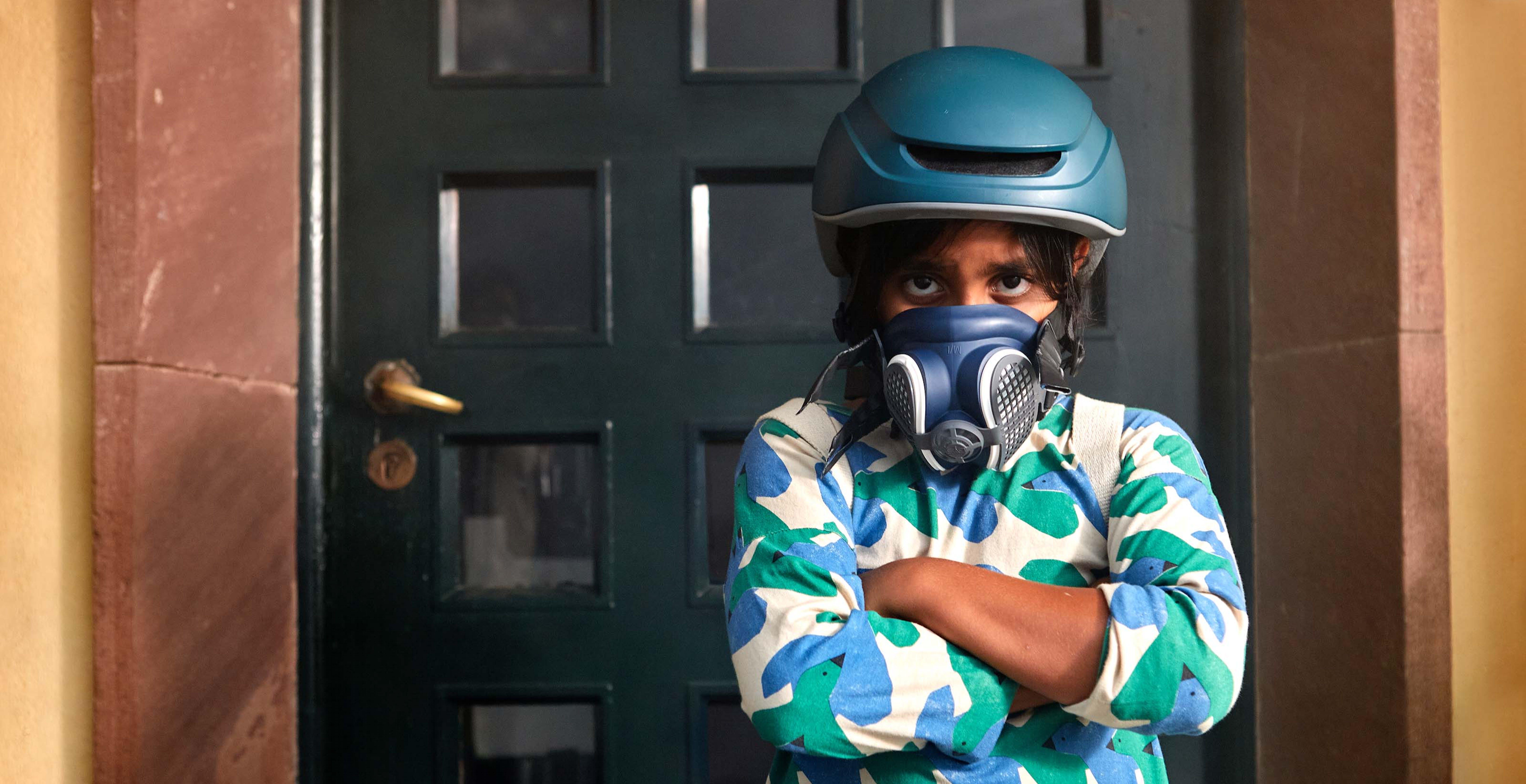 Spagna, una ragazza indossa un casco da bici e una maschera antigas per rappresentare il futuro catastrofico che attende i bambini se l'emergenza climatica dovesse peggiorare
