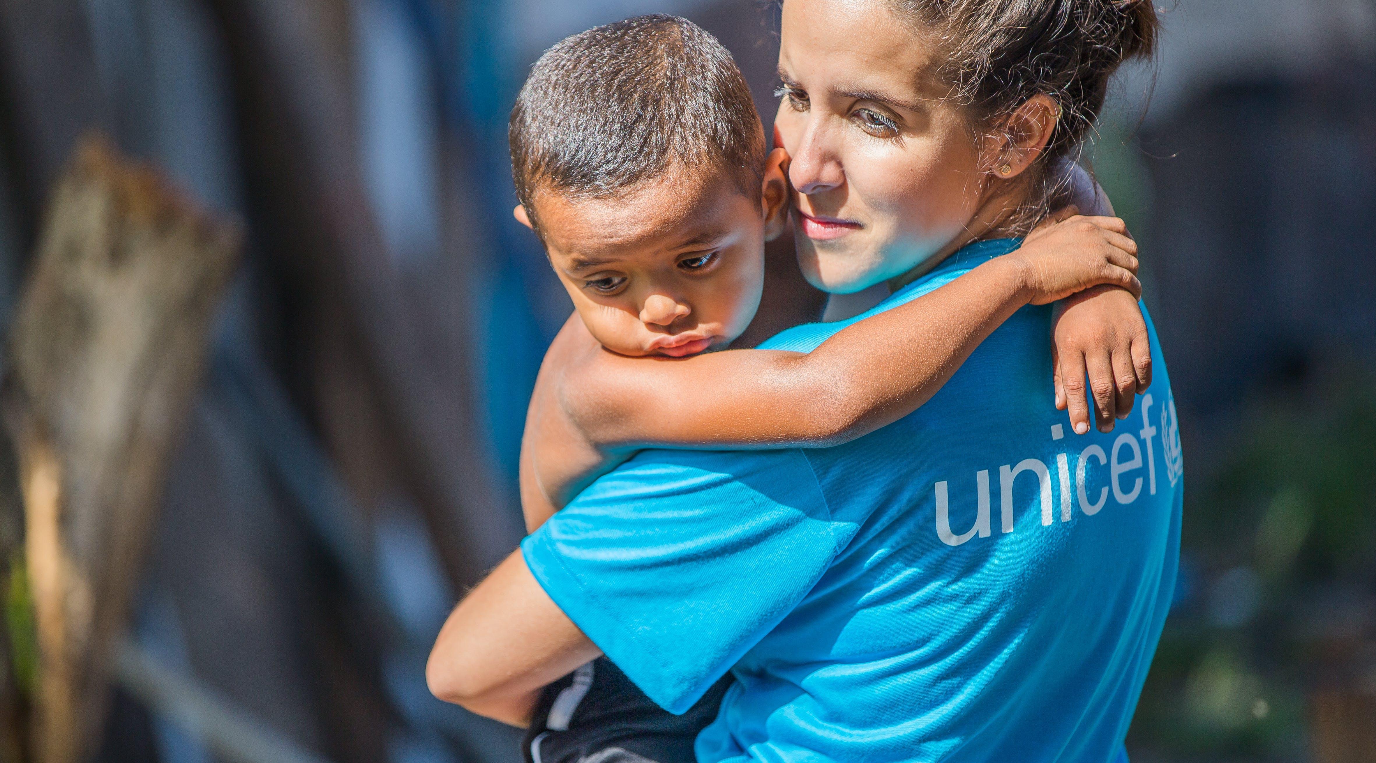 Brasile, un'operatrice UNICEF tiene in braccio un bambino.