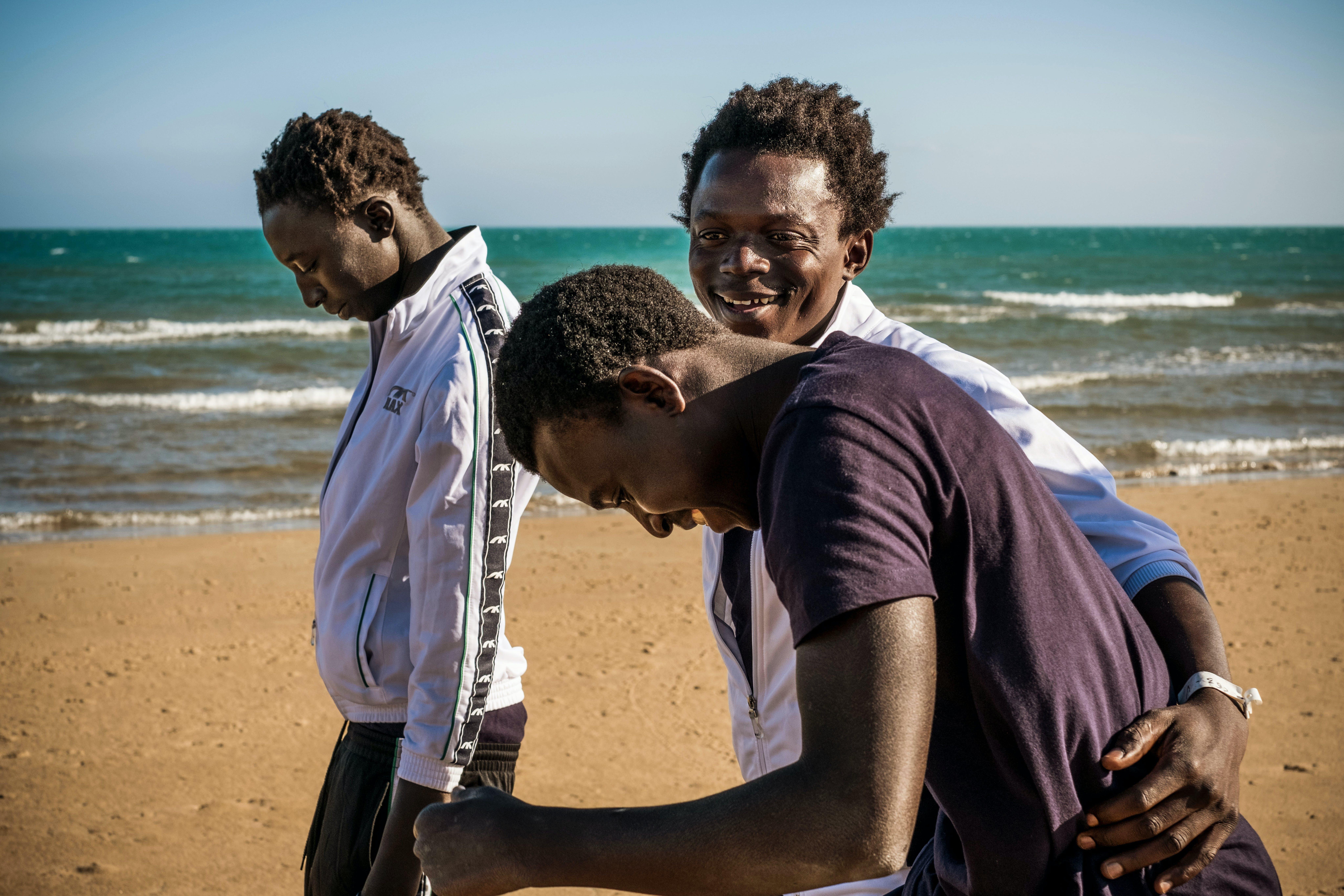 Mohammad (centro), 17, Sanna (destra), 17, e Fodaoi (sinistra), 14, camminano sulla spiaggia a Pozzallo, Sicilia. UNICEF/Gilbertson.