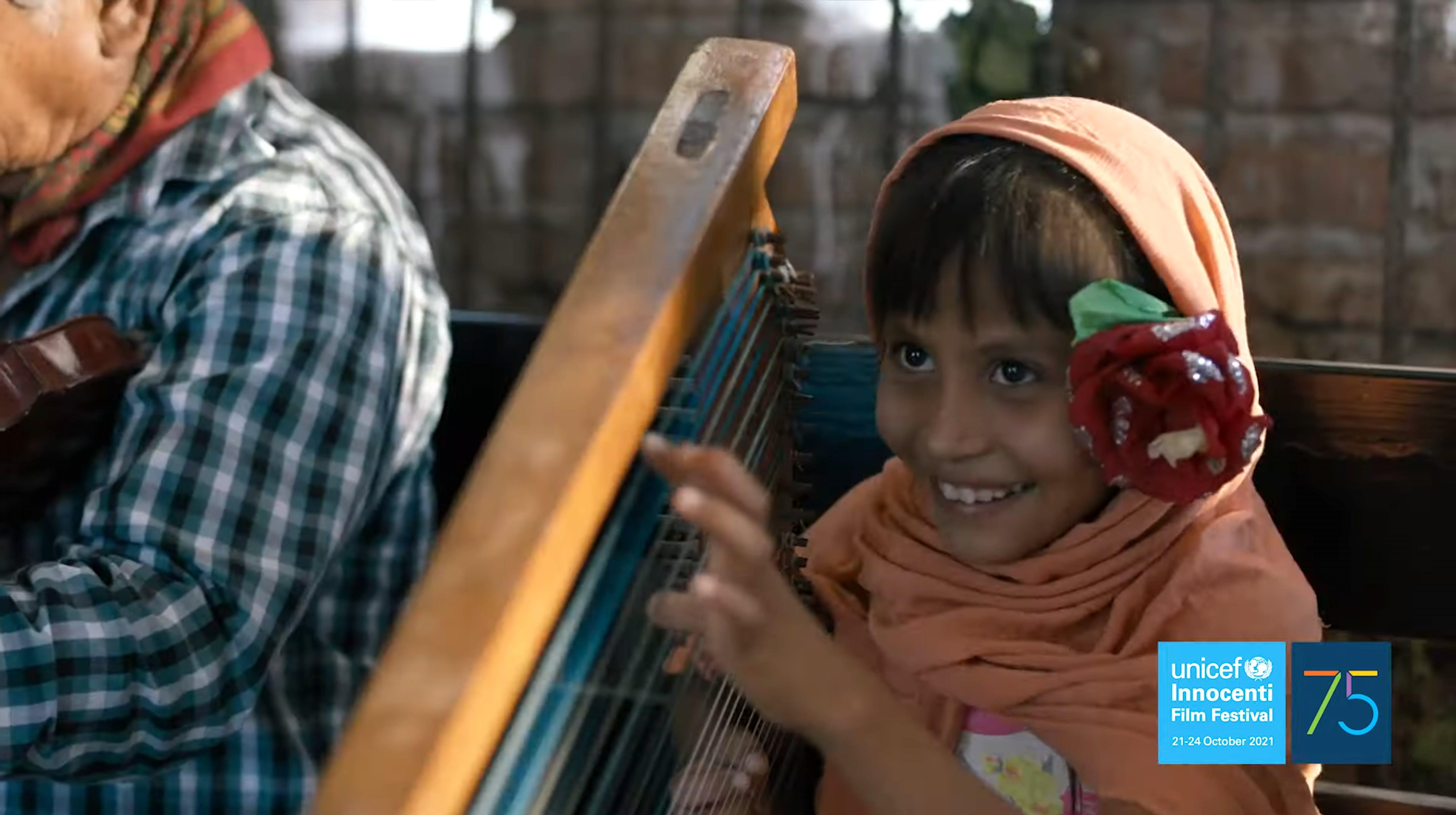 Frame di uno dei film dell'Innocenti Film Festival 2021 - bambina con arpa