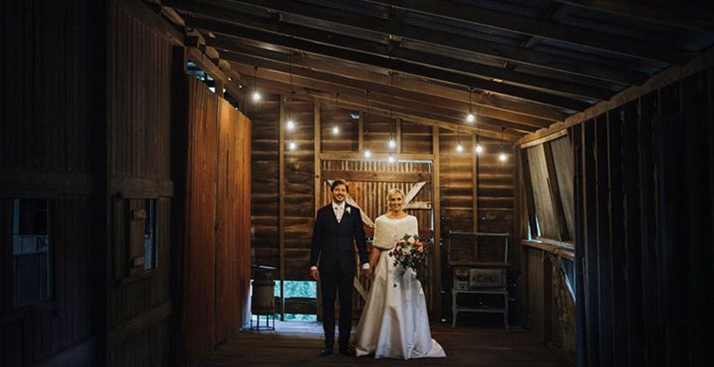 couple standing in rustic barn for wedding photo