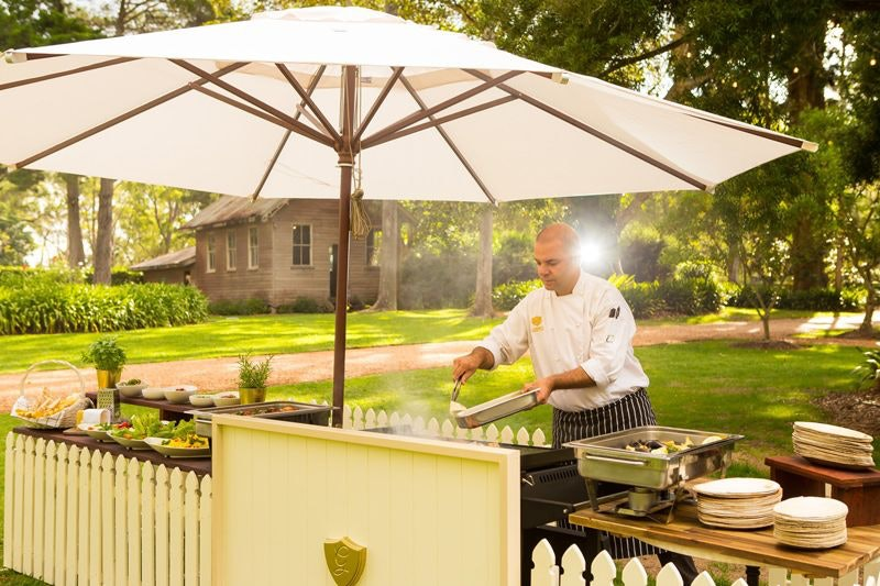Chef cooks on barbecue in front of Old School House at Gabbinbar Homestead
