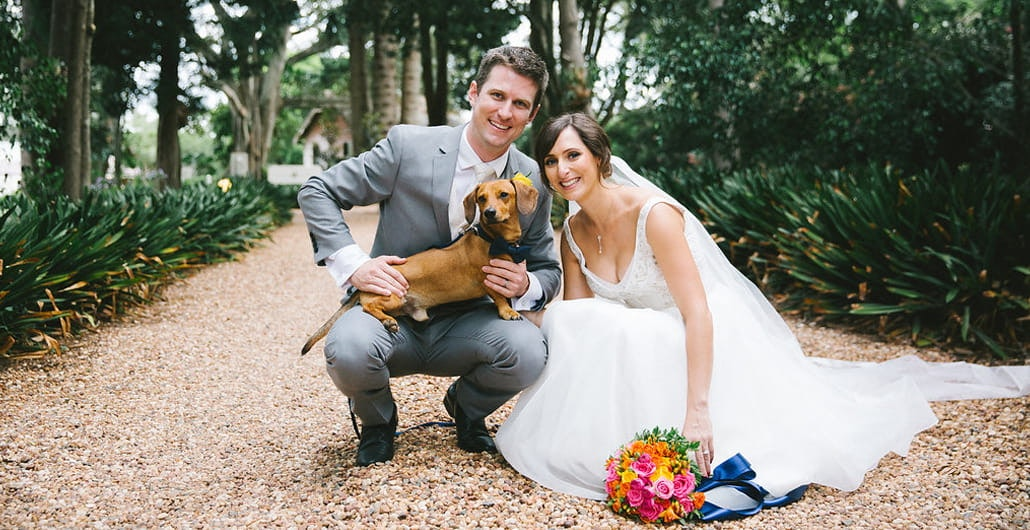 Couple pose at pet-friendly wedding venue with dog