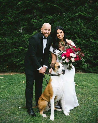 Newlywed couple pose with dog on wedding day