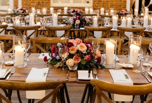 Tables and chairs set-up with arranged flowers and candles as centerpieces