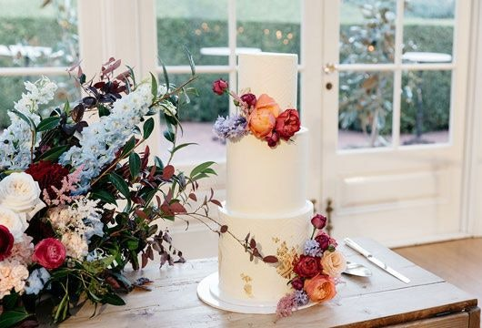 3 layered wedding cake on the table beside the arranged flowers