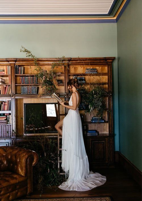 Bride Reading a book in library standing on a ladder