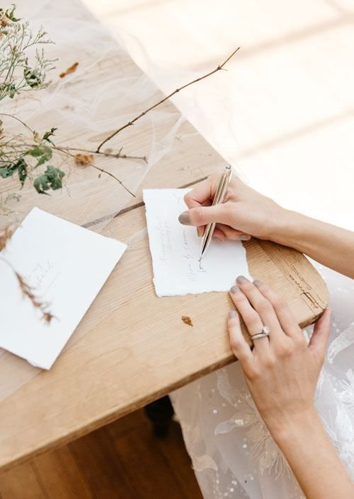 Bride writing on invitations