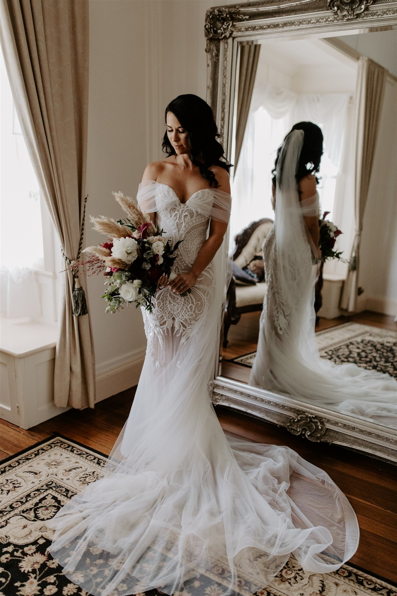 Bride stands in front of big mirror holding flowers