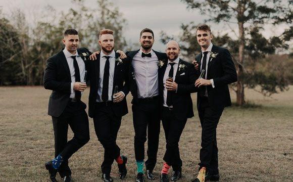 Happy groom with his groomsmen in the garden
