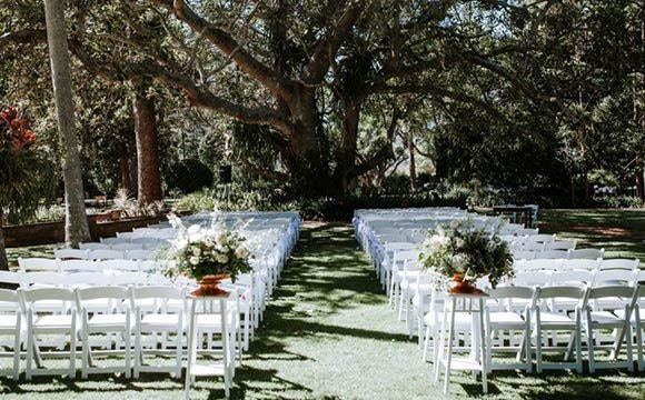 Wedding ceremony under tree with white chairs in a garden