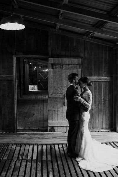 Groom giving his bride a forehead kiss inside the stable