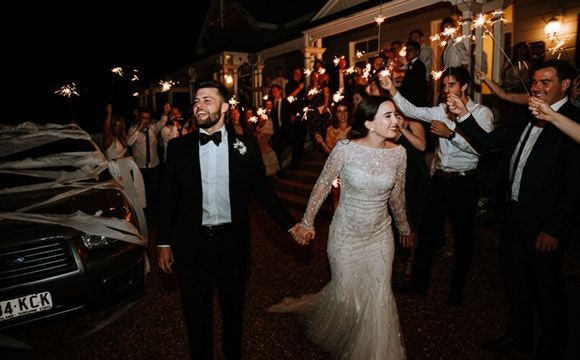 Newly-wed couple walking in the middle of wedding guests with sparklers