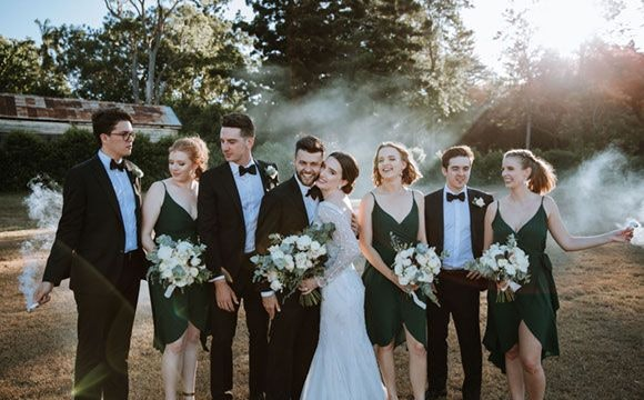 Bridal party in field with smoke