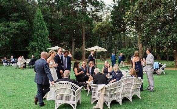 Visitors laughing with newlyweds in the garden