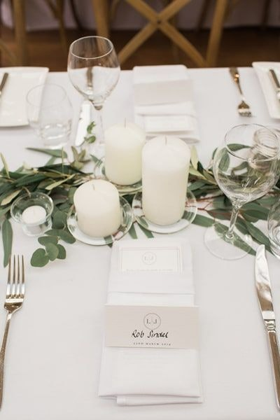 Wedding table decor with green foliage and candles