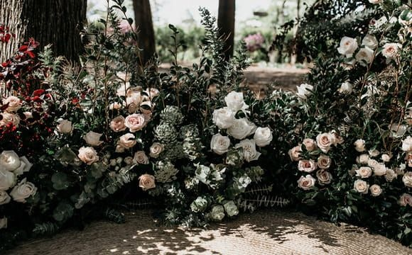 Wedding ceremony styling using white and peach coloured roses and lush green foliage