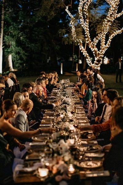 Happy guests talking to each other during outside wedding reception