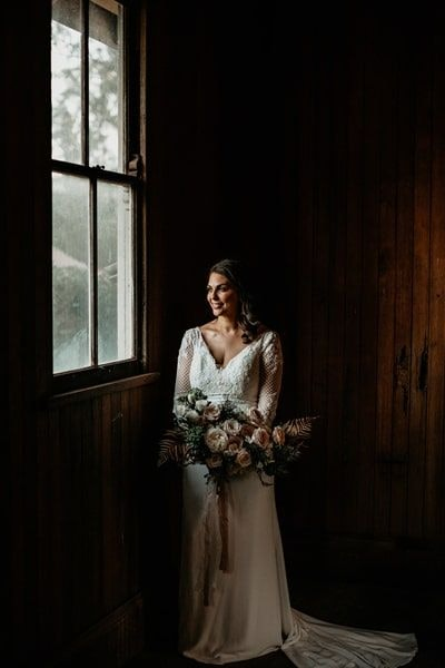 Bride holds bouquet and smiles out of window