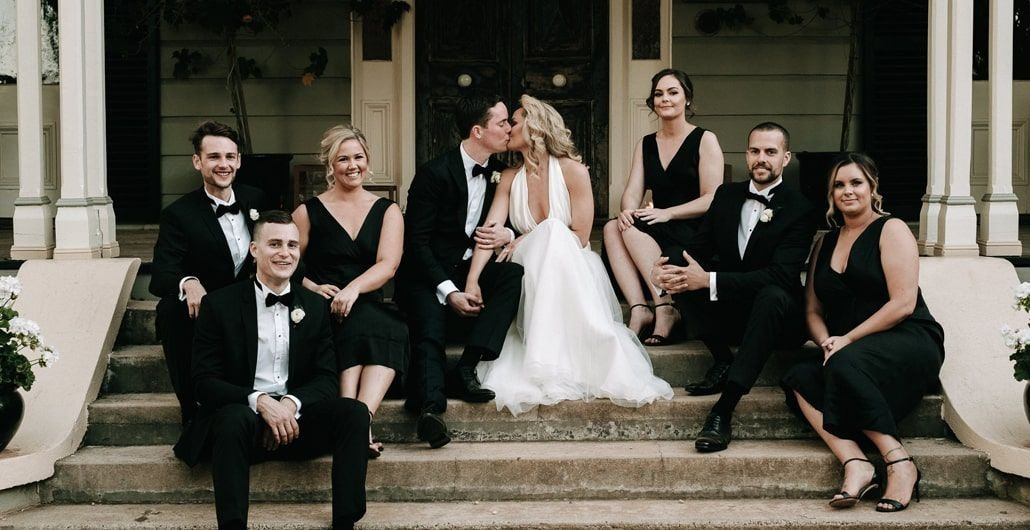 Stuart and Eden sitting with their bridal party