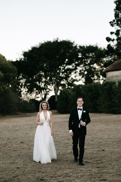 Bride and groom walking in the garden while holding a glass