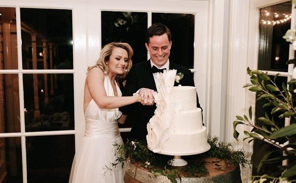 Stuart and Eden slicing their wedding cake