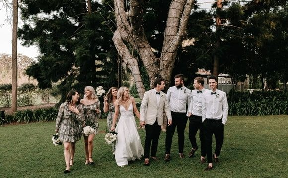 Bride and groom laughing with their bridesmaids and groomsmen while walking
