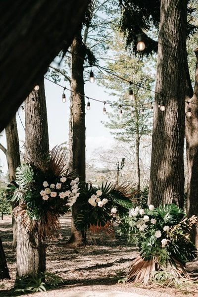 Ceremony flowers using green palm leaves and white flowers
