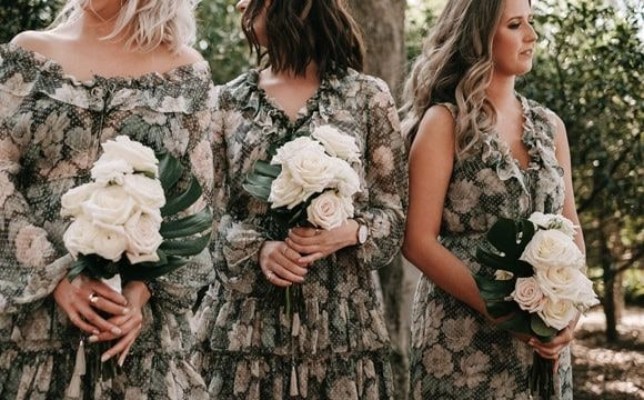 3 bridesmaids wearing floral green dress